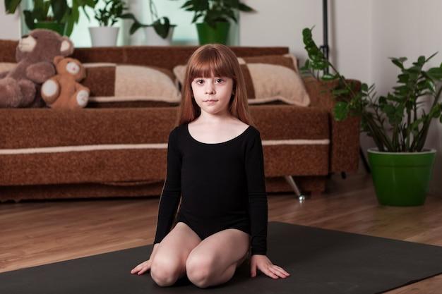 Юная гимнастка на ковре дома