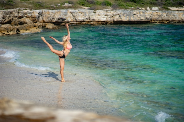 모래 해변에서 춤추는 젊은 체조 여자.