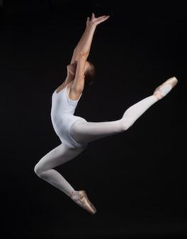 黒の背景に分離された白い体でジャンプ若い体操の女性