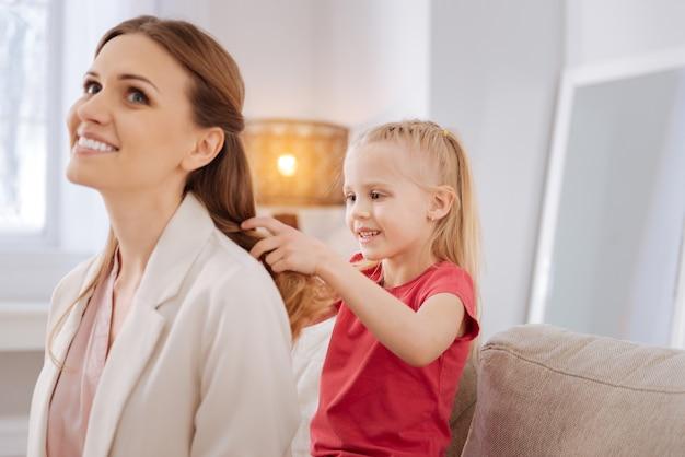 젊은 헤어 스타일리스트. 그녀의 어머니 뒤에 앉아 헤어 스타일을하는 동안 웃고 좋은 긍정적 인 행복 소녀