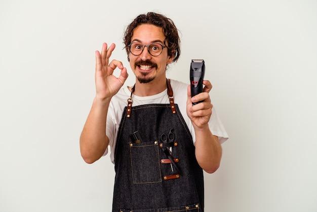 白い背景に孤立した若い美容師の白人男性は、陽気で自信を持って大丈夫なジェスチャーを示しています。