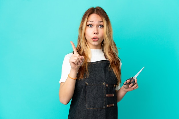 Young hairdresser girl over isolated blue background intending to realizes the solution while lifting a finger up