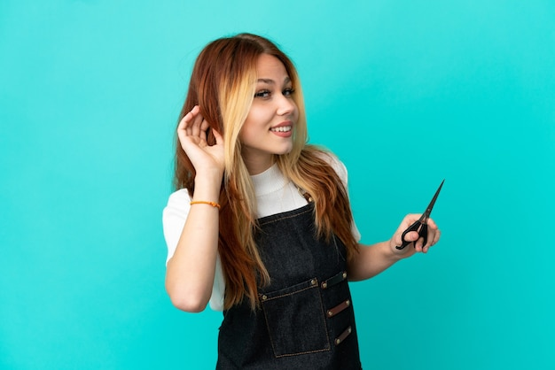Young hairdresser girl over isolated blue background listening to something by putting hand on the ear