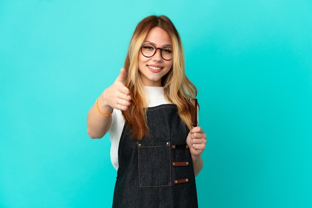 Young hairdresser girl over isolated blue background shaking hands for closing a good deal