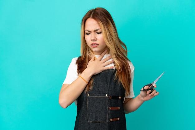많은 기침을 격리된 파란색 배경 위에 젊은 미용사 소녀