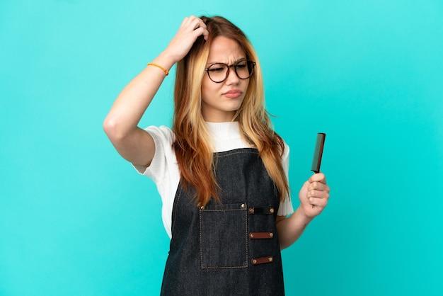 頭を掻きながら疑いを持っている孤立した青い背景の上の若い美容師の女の子