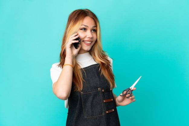 携帯電話との会話を維持している孤立した青い背景の上の若い美容師の女の子