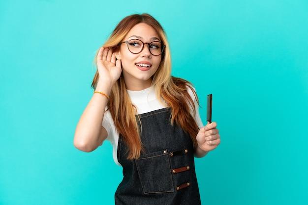 耳に手を置くことによって何かを聞いている孤立した青い背景の上の若い美容師の女の子