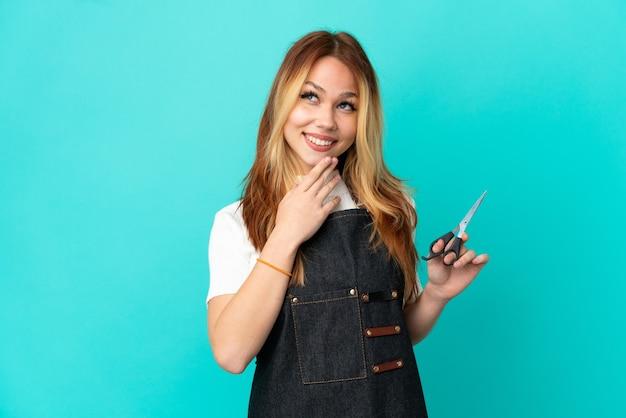 Молодая девушка парикмахер на изолированном синем фоне, глядя вверх, улыбаясь