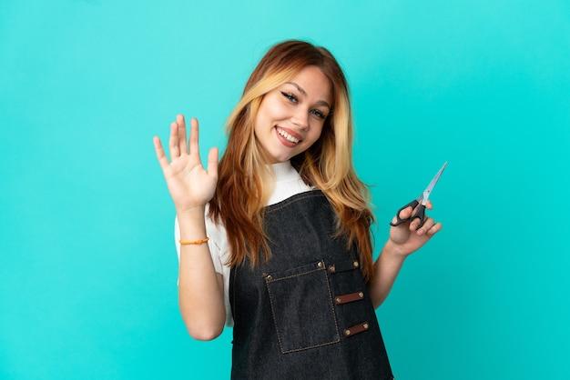 Молодая девушка-парикмахер на изолированном синем фоне, салютуя рукой с счастливым выражением лица