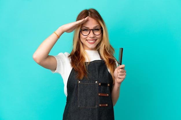 幸せな表情で手で敬礼する孤立した青い背景の上の若い美容師の女の子