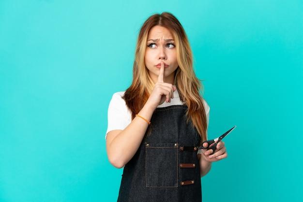 고립 된 파란색 배경 위에 젊은 미용사 소녀 입에 손가락을 넣어 침묵 제스처의 표시를 보여주는