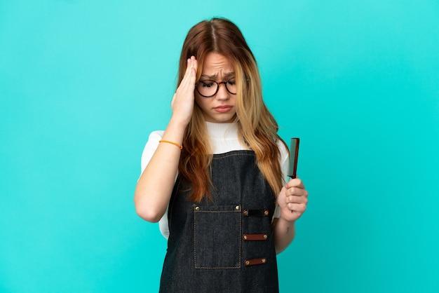 頭痛のある孤立した青い背景の上の若い美容師の女の子