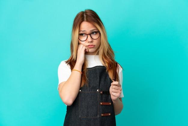 피곤하고 지루한 표정으로 고립 된 파란색 배경 위에 젊은 미용사 소녀