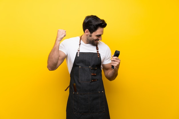 Young hairdresser man over isolated yellow wall celebrating a victory