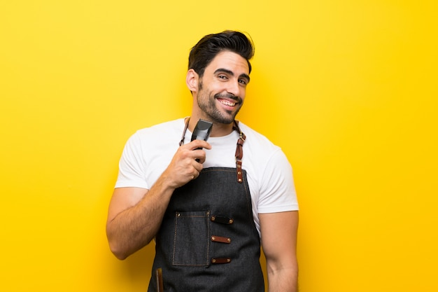 Young hairdresser man over isolated yellow wall