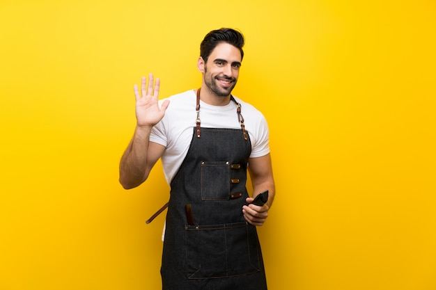 Young hairdresser man saluting with hand with happy expression