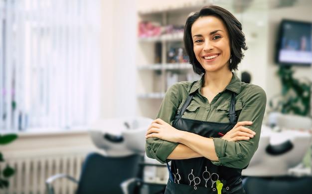 Молодой парикмахер. портрет профессионального парикмахера, смотрящего в камеру и улыбающегося со скрещенными руками, стоящего рядом с клиенткой, которая делает ей прическу.