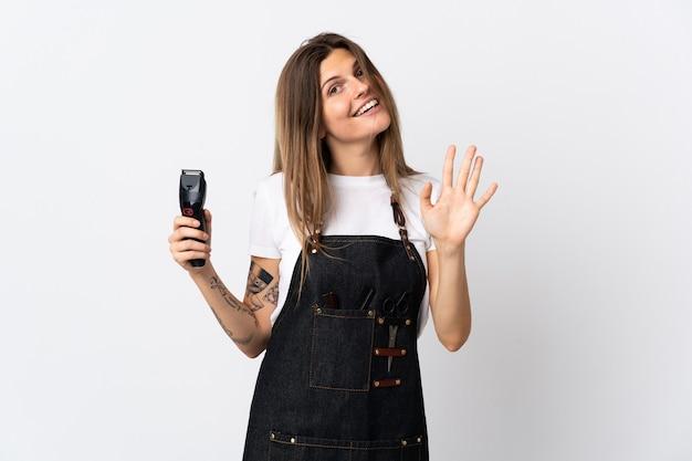 幸せな表情で手で敬礼する白い壁に分離された若い美容師スロバキア女性