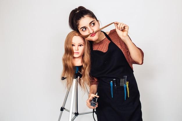 Молодой парикмахер с плойкой и манекен-головой на штативе