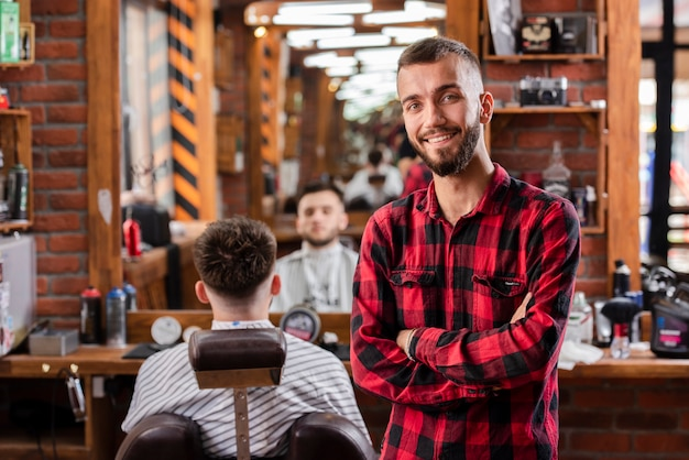 Young hairdresser with shirt smiling satisfied