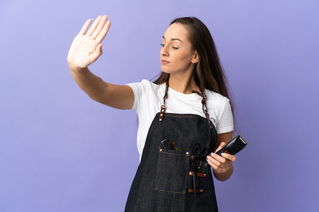 Young hairdresser woman over isolated background making stop gesture and disappointed