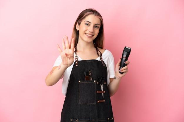 幸せなピンクで隔離され、指で4を数える若い美容師の女性