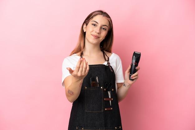ピンクで隔離された若い美容師の女性が手で来るように誘う