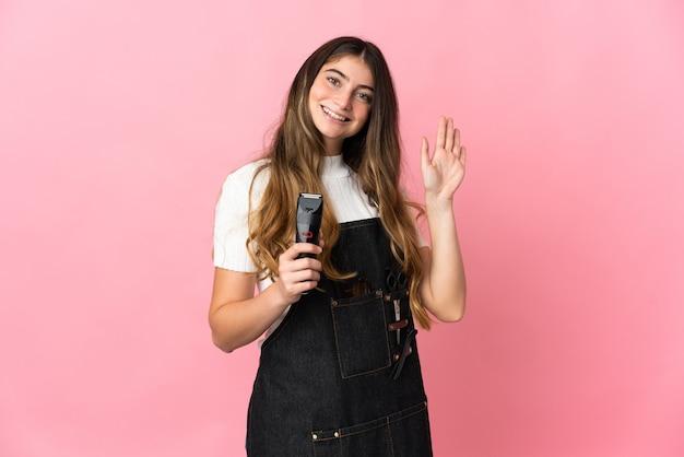 幸せな表情で手で敬礼ピンクに分離された若い美容師の女性 Premium写真