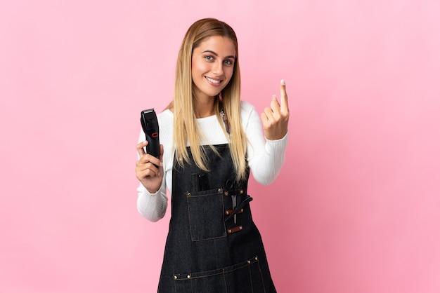 Молодая женщина-парикмахер изолирована на розовой стене, делая приближающийся жест