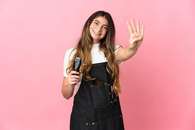 幸せなピンクの壁に隔離され、指で4を数える若い美容師の女性