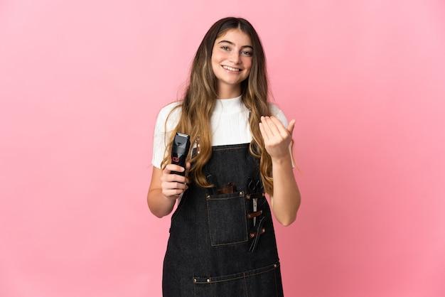 ピンクの壁に孤立した若い美容師の女性が手で来るように誘う。あなたが来て幸せ
