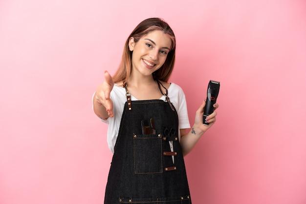 Молодая женщина-парикмахер изолирована на розовой стене, пожимая руку для заключения хорошей сделки