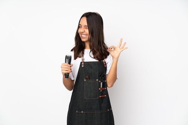 指でokサインを示す白い背景で隔離の若い美容師の女性