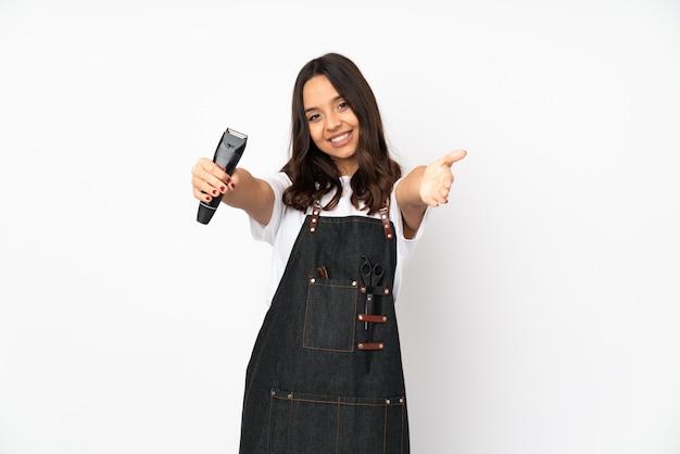 Молодая женщина парикмахер, изолированных на белой стене, представляя и приглашая прийти с рукой