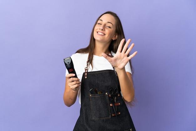 손가락으로 5 세 격리 된 배경 위에 젊은 미용사 여자
