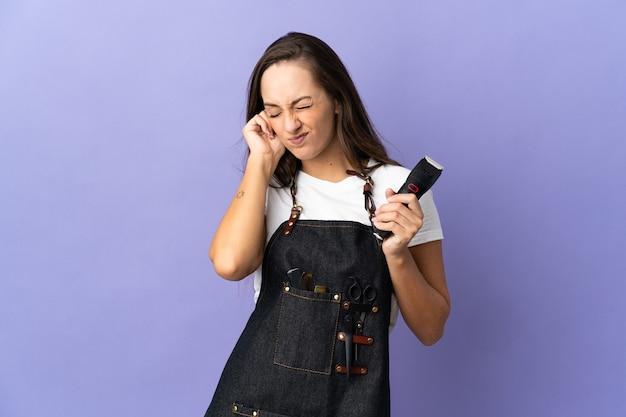欲求不満と耳を覆っている孤立した背景上の若い美容師の女性