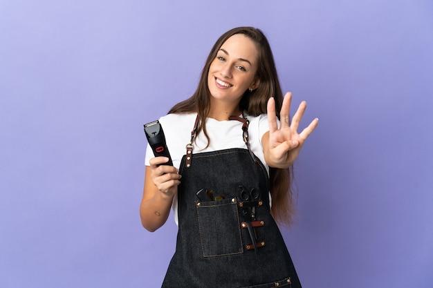 幸せで、指で4を数える孤立した背景上の若い美容師の女性