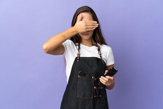 手で目を覆っている孤立した上の若い美容師の女性。何かを見たくない