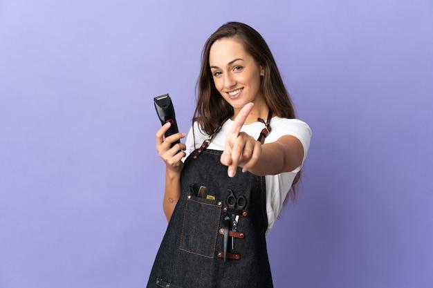 指を見せて持ち上げる孤立した上の若い美容師の女性