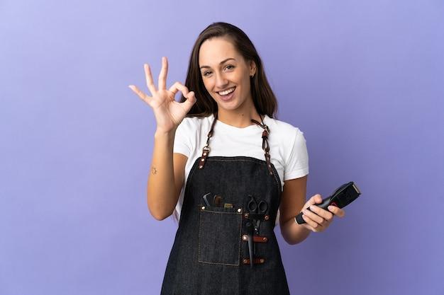 指でokサインを示している孤立した上の若い美容師の女性