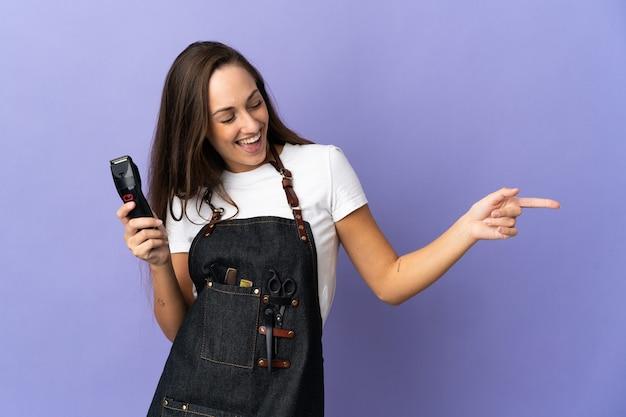 측면에 손가락을 가리키고 제품을 제시하는 격리 된 벽 위에 젊은 미용사 여자