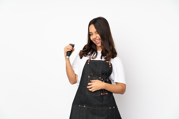 Young hairdresser woman on white wall making guitar gesture
