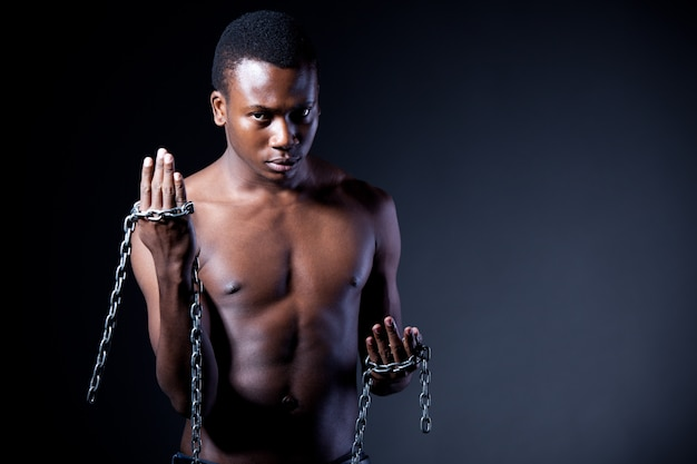 Young half naked  man standing and holding massive chains in hands