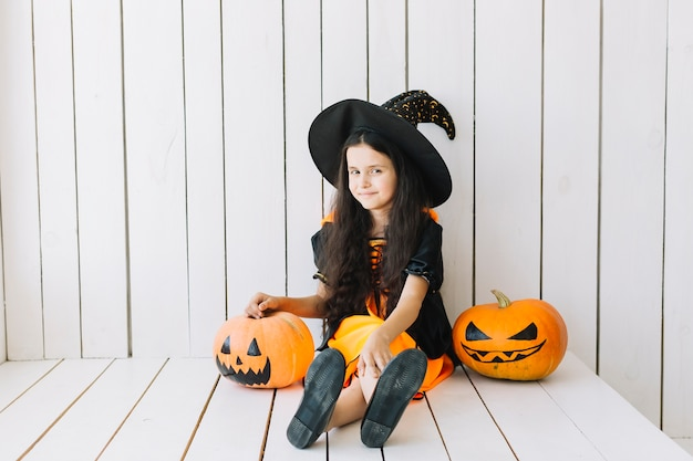 Young halloween witch and jack-o-lanterns