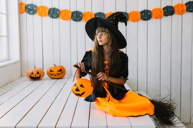 Young halloween witch with pumpkin lantern and broom