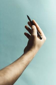 Молодая рука сжимает механический карандаш на пастельно-синем фоне с глубокими тенями