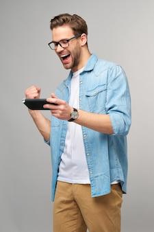 회색 벽 위에 서있는 휴대용 비디오 게임을 가지고 노는 젊은 handcome 남자