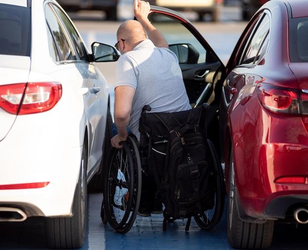 車椅子の赤い車に乗る若い障害者ドライバー