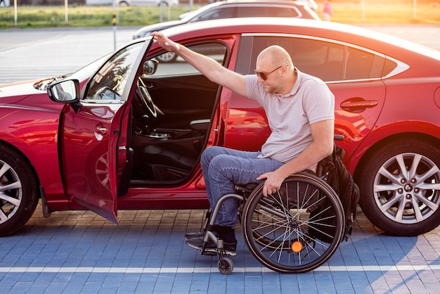 Молодой водитель-инвалид садится в красный автомобиль из инвалидной коляски
